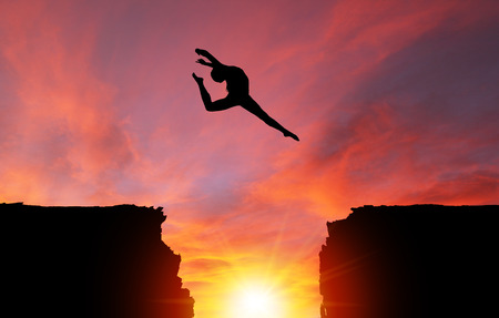 Silhouette of girl dancer in a stag split leap over dangerous cliffs with dramatic sunset or sunrise background and copy space. Concept of faith, conquering adversity, taking risk; challenge, courage, determination or achievement.