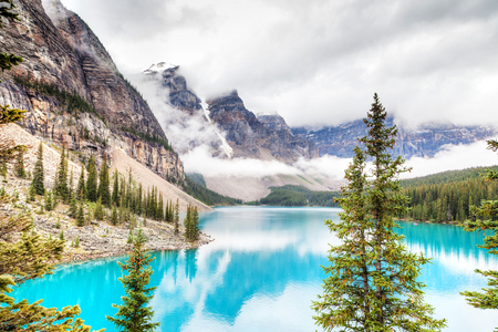 Fog and clouds descend onto the Valley of Ten Peaks where glacier-fed Moraine Lake gives off its distinct turquoise blue color due to refraction of light off the rock flour at the bottom of the lake.