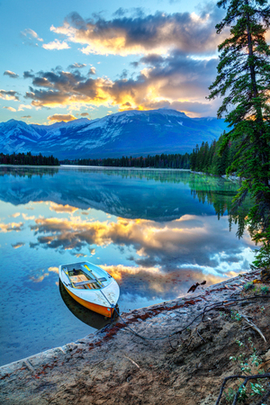 Morning sun breaks out over the Rocky Mountains at Edith Lake in Jasper National Park, with a boat in the foreground. Stock Photo