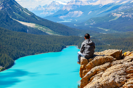 A hiker sitting on the edge of Bow Summit looking at Peyto Lake in Banff National Park on the Icefields Parkway. The glacier-fed lake is famous for its bright turquoise colored waters in the summer.