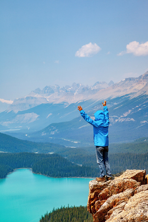 A hiker standing on the edge of Bow Summit overlooking Peyto Lake in Banff National Park on the Icefields Parkway. The glacier-fed lake is famous for its bright turquoise colored waters in the summer.