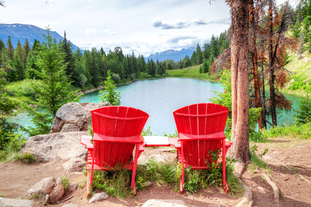 Two red adirondack chairs overlooking the Valley of the Five Lakes on the Icefields Parkway in the Canadian Rockies. They were placed by Parks Canada in select scenic locations throughout Jasper National Park for visitors to enjoy the exquisite mountain and lakeside vistas. Stock Photo