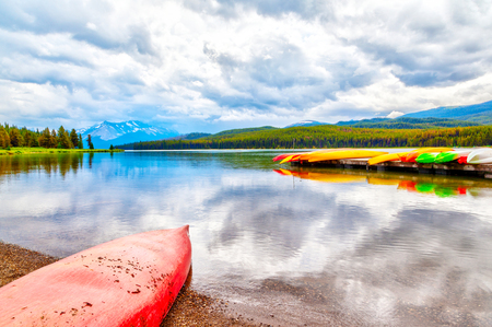 Colorful canoes lie on the dock at Maligne Lake in Jasper National Park, Alberta, Canada. The lake is famous for the surrounding peaks and the three visible glaciers.