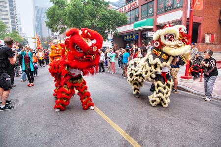 CALGARY, CANADA - SEP 4, 2018: A crowd watching a Chinese lion dancing parade along Chinatown in Calgary, Alberta, Canada, in celebration of Chinese festivities. Editorial