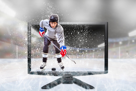 Junior ice hockey player in competitive sports gear standing inside brightly lit outdoor stadium on TV monitor. Concept of realistic Live 3D televison or Virtual Reality sports.