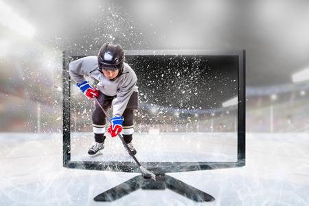 Jugador de hockey sobre hielo junior en equipo deportivo competitivo de pie dentro del estadio al aire libre iluminado en el monitor de TV. Concepto de televisión 3D en vivo realista o deportes de realidad virtual.