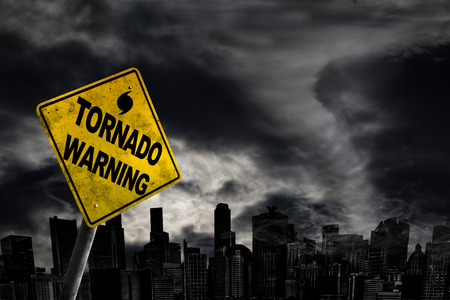 Tornado warning sign against a powerful stormy background with city silhouette and copy space. Dirty and angled sign with cyclonic winds add to the drama.