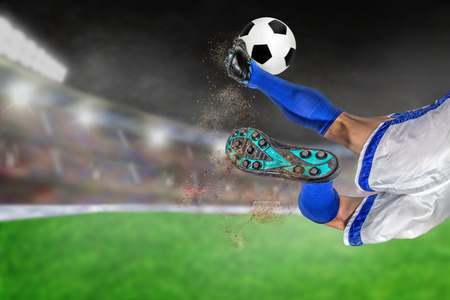Soccer player with spectacular scissor kick of football in brightly lit outdoor stadium. Focus on foreground and soccer ball with shallow depth of field on background and copy space.