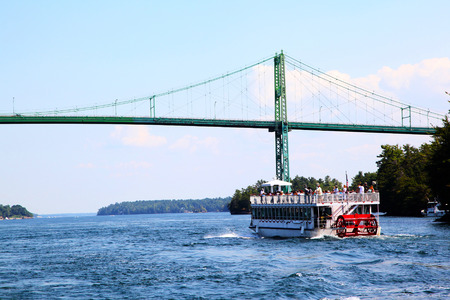 A cruise boat approaches the Thousand Islands International Bridge on the St. Lawrence River connecting New York, USA, with Ontario, Canada in the middle of the 1000 Islands region. 免版税图像