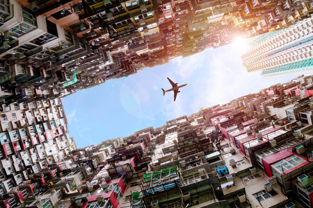 Plane flying dramatically overhead in Hong Kong's old densely residential housing district of Quarry Bay with deliberate lens flare.
