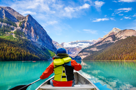 Teen boy canoeing on Lake Louise in Banff National Park of the Canadian Rockies with its glacier-fed turquoise lakes and Mount Victoria Glacier in the background.