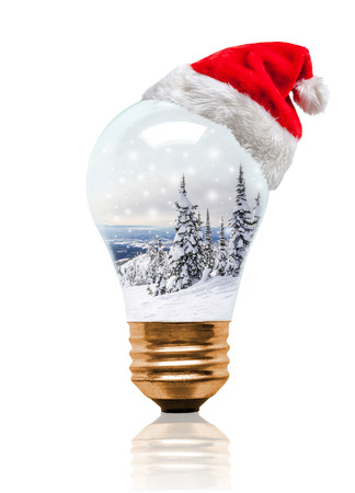 Snow globe light bulb wearing Santa hat with Christmas Winter scene with copy space. Glowing Xmas season and bright New Year.
