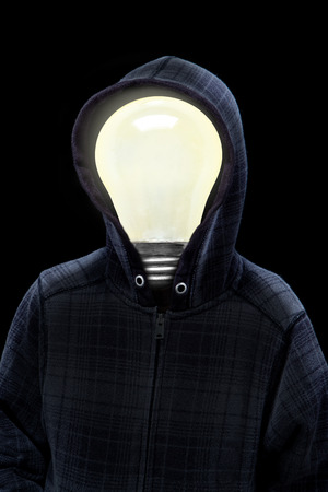 Mysterious man wearing hoodie in silhouette with a light bulb on his head isolated on black background. Concept of mystery, creativity, bright ideas, intelligence.