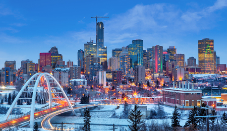 Edmonton downtown Winter skyline just after sunset at the blue hour showing Walterdale Bridge across the frozen, snow-covered Saskatchewan River and surrounding skyscrapers. Edmonton is the capital of Alberta, Canada. Stockfoto