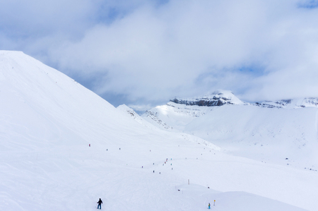 Unidentifiable skiers and snowboarders at a distance going down a mountain slope in Lake Louise in the Canadian Rockies of Alberta, Canada.