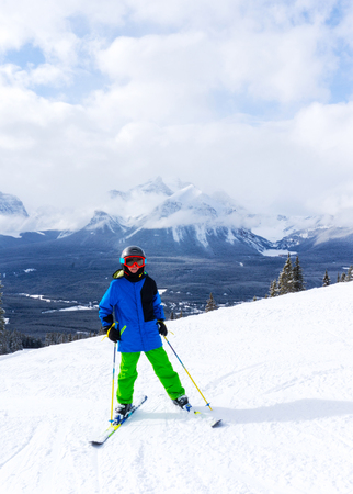 Young skier at the top of a mountain range in Lake Louise in the Canadian Rockies of Alberta, Canada. 写真素材
