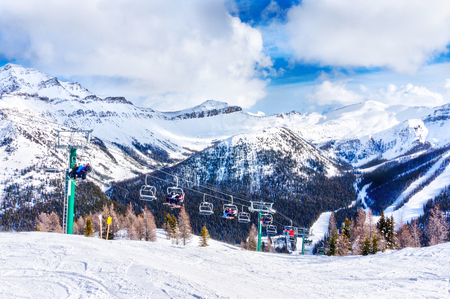 Unidentifiable skiers and snowboarders on chairlift going up a ski slope in the snowy mountain range of the Canadian Rockies.