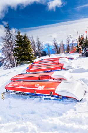 Rows of ski patrol toboggans or rescue sleds lie on snow on mountain ski resort. Also known as akia or emergency rescue sledg, it is used by mountain rescue teams in winter to evacuate an injured skier or snowboarder.