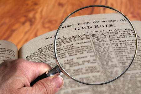 Hand holding magnifying glass over an old Bible opened to the famous chapter of Genesis. This translation is King James, which is public domain.