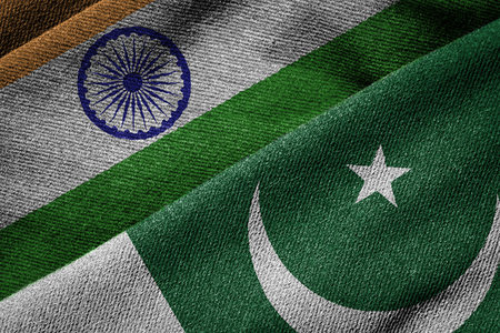 Overlapping grunge flags of India and Pakistan,  highlighting the ongoing political tension and conflict between the two neighboring countries since 1947.