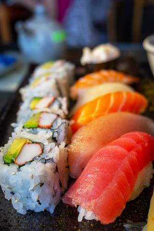Delicious Japanese nigiri sushi bento with Tuna Toro, Tuna Ahi, Salmon Sake, Yellowtail Hamachi, Shrimp Ebi, and California roll. Vertical orientation.