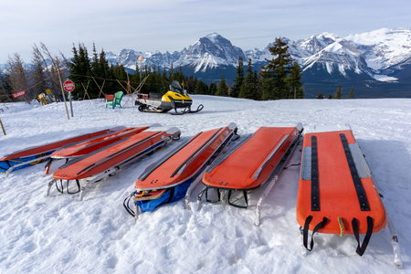 Rows of ski patrol toboggans or rescue sleds lie on snow on mountain ski resort. Also known as akia or emergency rescue sledg, it is used by mountain rescue teams in winter to evacuate an injured skier or snowboarder. Foto de archivo - 123218725