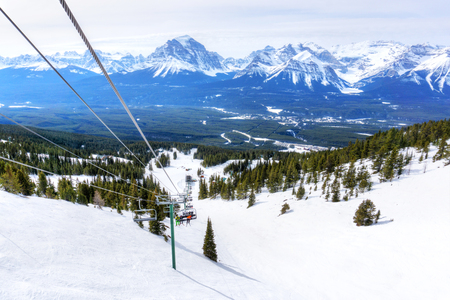 Unidentifiable skiers on chairlift going up a ski slope in the snowy mountain range of the Canadian Rockies. 스톡 콘텐츠