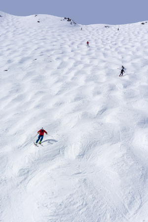 Skiers descending the steep mogul ski hill slope at a mountain in Lake Louise in the Canadian Rockies of Alberta, Canada.