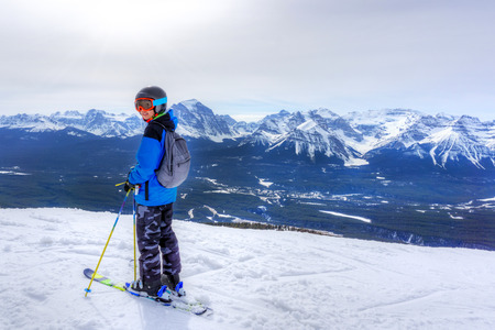 Young skier standing at the edge of a mountain range in Lake Louise at the Canadian Rockies of Alberta, Canada. Imagens