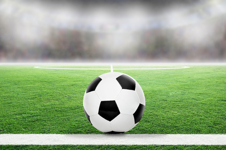Soccer on football stadium field with blurred crowd background and copy space.