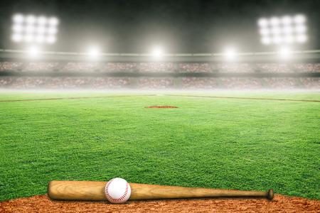 在灯火通明的户外体育场上的棒球棒和球。关注前景,背景和复制空间的浅景深。