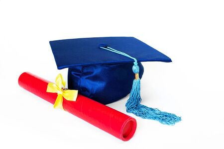 Tapa de graduación azul o birrete con borla azul y diploma en caso con cinta amarilla, aislado sobre fondo blanco. Foto de archivo