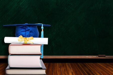 Education concept with blue graduation hat and diploma on stack of books on blackboard background. Copy space on chalk board.