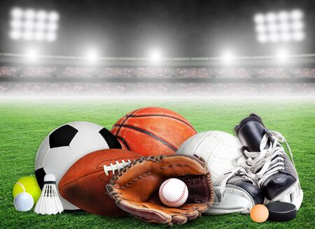 Sports equipment, rackets and balls for all seasons in stadium background with copy space.