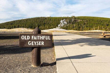 Old Faithful Geyser sign at Yellowstone National Park with steam emitting from the geyser in the background.