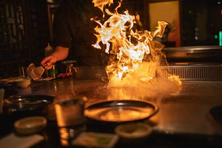 Teppanyaki chef preparing metal plate with flaming fire ready for cooking Japanese cuisine.