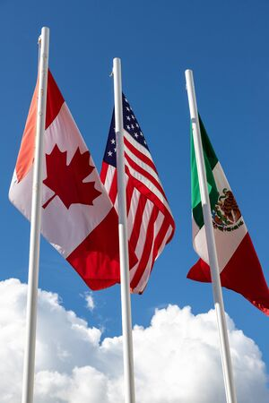 Flags of United States, Mexico, Canada flying together, concept of new NAFTA agreement now known as USMCA in the U.S., CUSMA in Canada or T-MEC in Mexico.