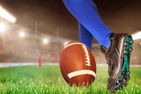 American football player prepares to kick ball for conversion points or field goal in brightly lit outdoor stadium with focus on foreground and shallow depth of field on background. Stock Photo