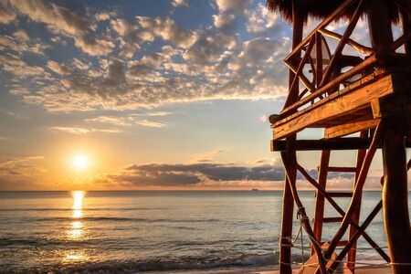 Sunrise over tropical beaches of Riviera Maya near Cancun, Mexico, with lifeguard tower overlooking the Caribbean Sea.