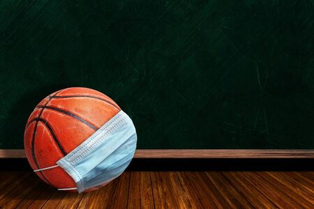 Basketball wearing surgical mask on a background chalk board with copy space for text. Concept of COVID-19 coronavirus pandemic affecting basketball seasons due to game or league suspensions or cancellations. Stock fotó