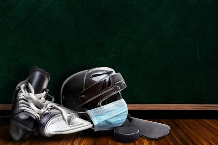 Ice hockey helmet wearing surgical mask on a background chalk board with copy space for text. Concept of COVID-19 coronavirus pandemic affecting ice hockey season due to game or league suspensions or cancellations. Stock fotó