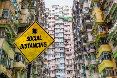 Social Distancing warning sign in front of a crowded public housing estate in Quarry Bay, Hong Kong. Concept of importance of physical distancing to prevent COVID-19 coronavirus spread especially in a densely populated city.