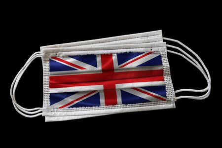 Multiple surgical face masks with UK flag printed. Isolated on black background. Concept of face mask usage in the British effort to combat Covid-19 coronavirus pandemic.