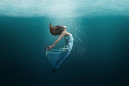 Elegant girl dancer in white dress in a state of levitation under the deep waters of the ocean with sunlight beaming on her face.