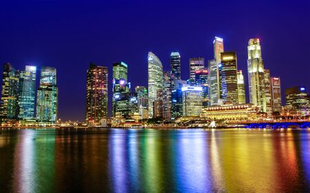 Singapore skyline of downtown city business district at twilight blue hour with colorful reflections on Marina Bay waterway.