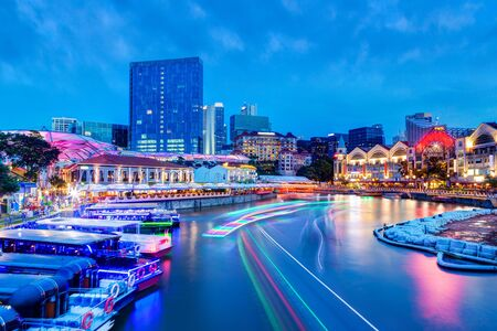 Sunset night life at Clarke Quay on Singapore River as colorful light trails from river boats and surrounding bars and restaurants light up the popular tourist area that used to be a commercial warehouse center during the colonial era.