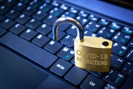 COVID-19 coronavirus lockdown restrictions ease concept illustrated by unlocked padlock on laptop.
