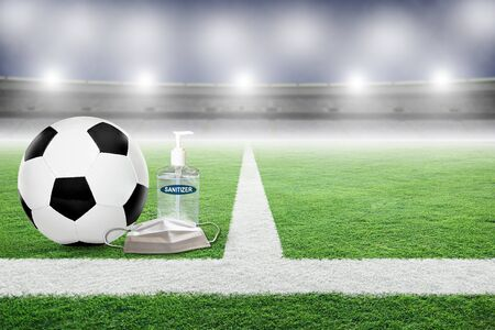 Soccer on field of an empty stadium with hand sanitizer and medical face mask. Concept of football played without fans as part of social distancing to prevent spread of COVID-19 coronavirus in the New Normal. Imagens