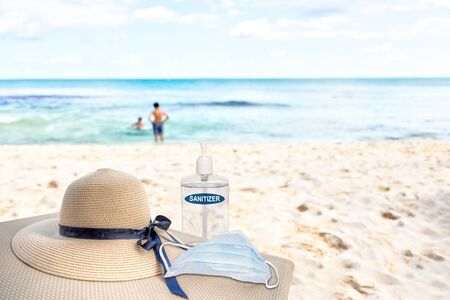 Vacationing in the New Normal after COVID-19 coronavirus pandemic. Tourism concept showing lounge chair on sandy beach with beach hat, hand sanitizer, medical face mask and copy space. 스톡 콘텐츠
