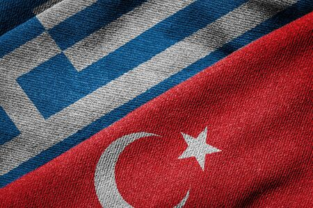 3D rendering of the flags of Greece and Turkey woven fabric texture. Detailed textile pattern and grunge theme. Concept of relations between the two countries marked by alternating periods of mutual hostility and reconciliation. Archivio Fotografico